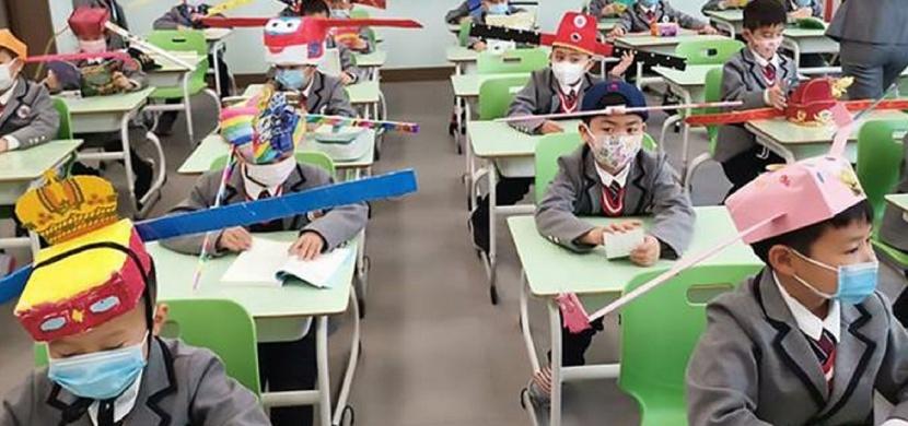 Povinné odstupy ve školách jako ochrana před koronavirem: Školáci v čínském Chang-čou nosí speciální čepice s metrovými tyčemi